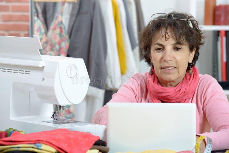 研究膝上型计算机的可爱的时装设计师 免版税图库摄影