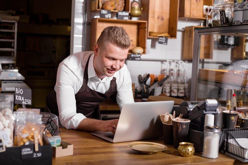 研究膝上型计算机的咖啡馆所有者 免版税图库摄影