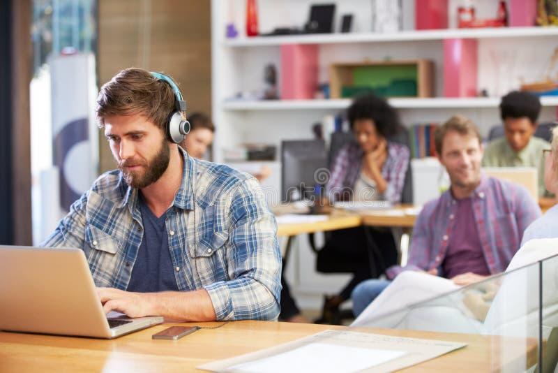 研究膝上型计算机的商人佩带的耳机在办公室 库存图片