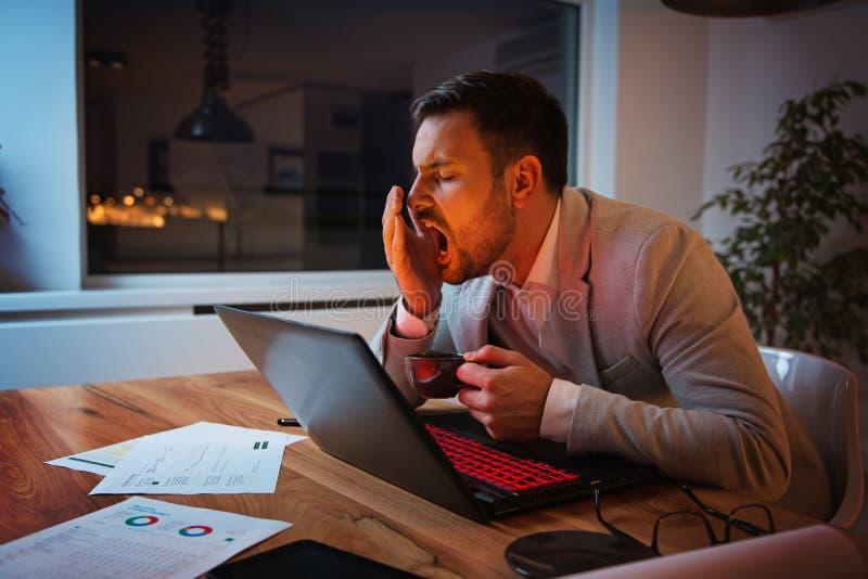 研究膝上型计算机的商人,劳累过度,在压力下 图库摄影