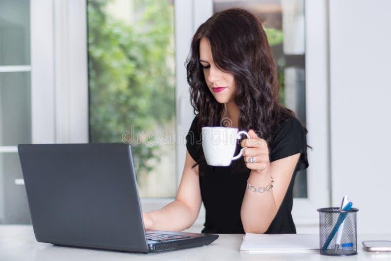 研究膝上型计算机的女商人在办公桌和饮用的咖啡 库存照片