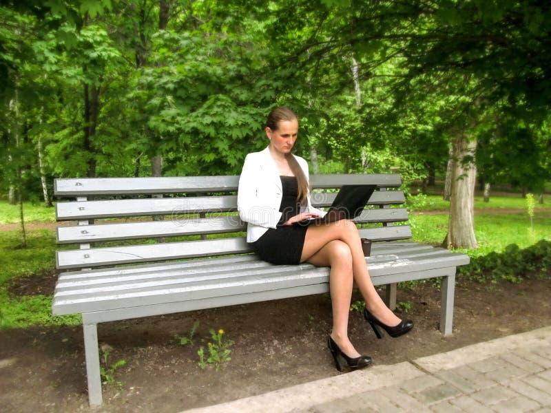 研究膝上型计算机的女实业家坐一条长凳在公园 一件小的黑礼服,白色夹克的逗人喜爱的年轻成人女孩和 免版税库存图片