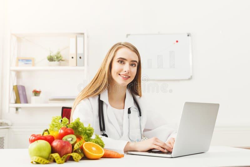 研究膝上型计算机的女性营养师 免版税库存照片