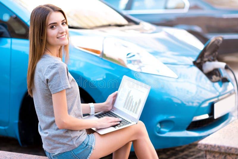 研究膝上型计算机的妇女在混合动力车辆附近 免版税库存照片