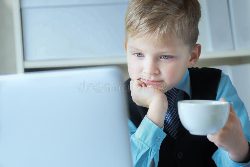 研究膝上型计算机的小企业男孩拿着白色咖啡或热的茶 r ??  库存照片