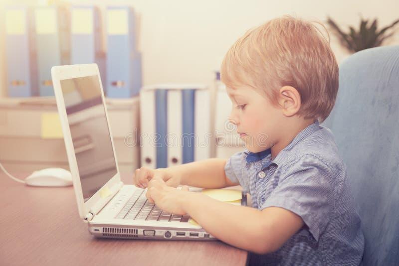 研究膝上型计算机的小男孩 库存图片