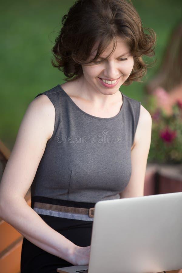 研究膝上型计算机的少妇在公园 库存图片