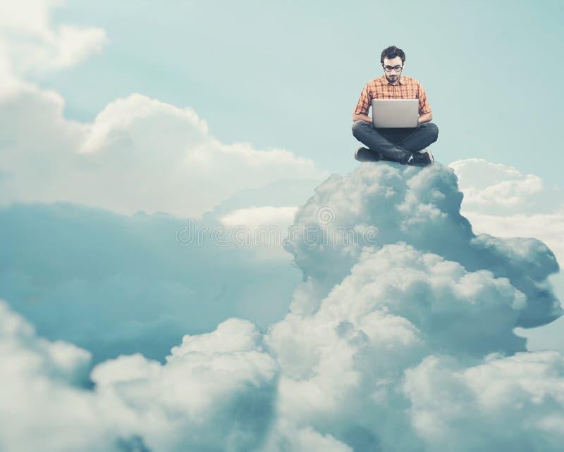研究膝上型计算机的少年和在云彩上升 免版税库存照片