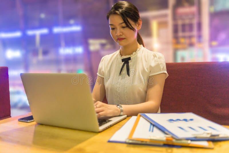 研究膝上型计算机的年轻亚裔妇女在晚上 库存图片