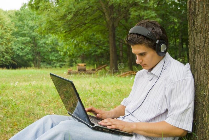 研究膝上型计算机的年轻人在公园 免版税图库摄影