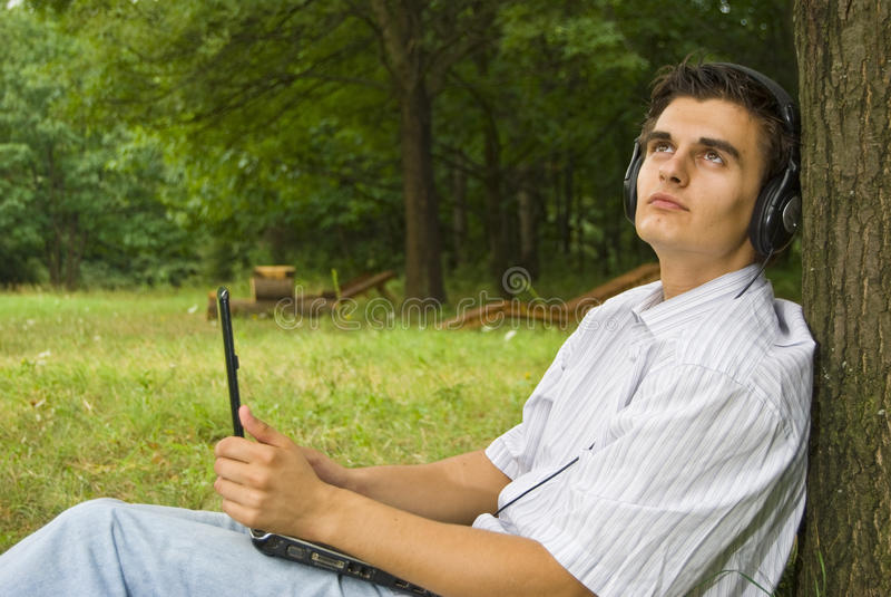研究膝上型计算机的年轻人在公园 免版税库存照片