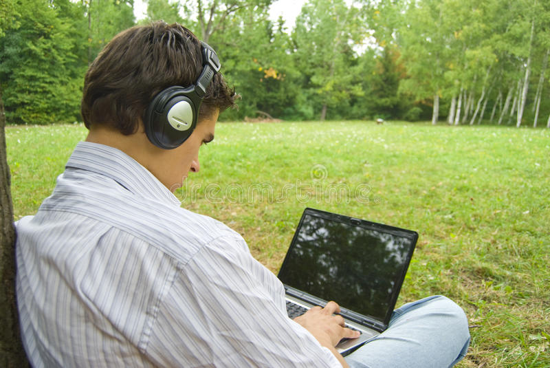 研究膝上型计算机的年轻人在公园 免版税库存图片