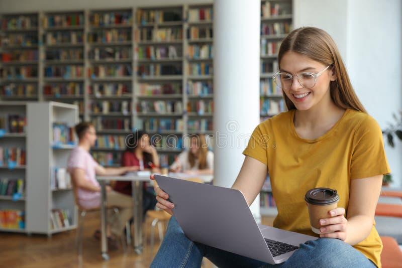 研究膝上型计算机的年轻女人在图书馆里 免版税图库摄影