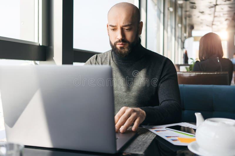 研究膝上型计算机的年轻有胡子的商人,当坐在咖啡馆时 自由职业者在现代coworking遥远地工作 ( 免版税库存照片