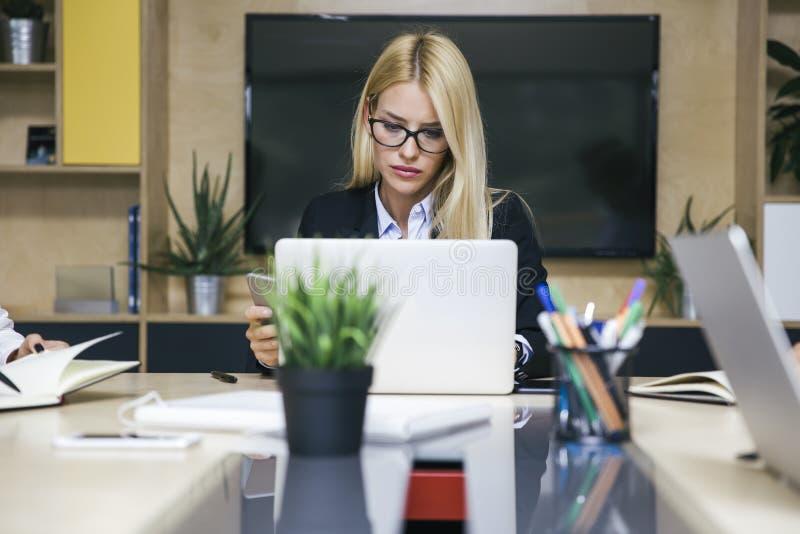 研究膝上型计算机的年轻白肤金发的妇女在办公室 免版税库存照片