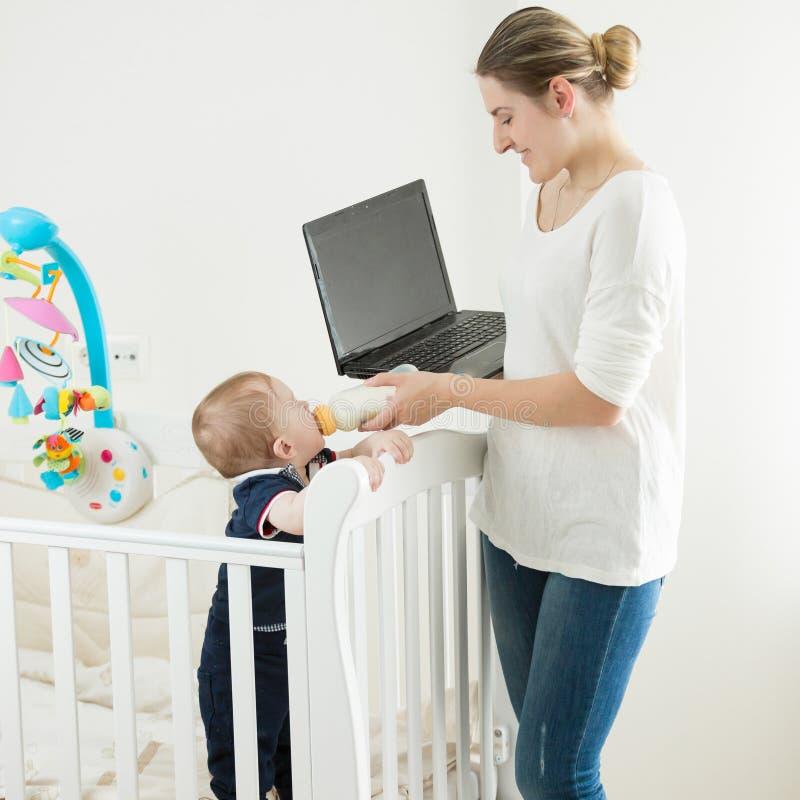研究膝上型计算机的年轻自的emploed妇女画象,当喂养她的小儿子用从瓶时的牛奶 免版税库存照片