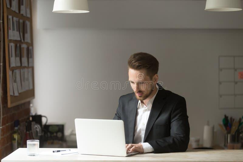 研究膝上型计算机的年轻英俊的商人在现代办公室 免版税库存照片
