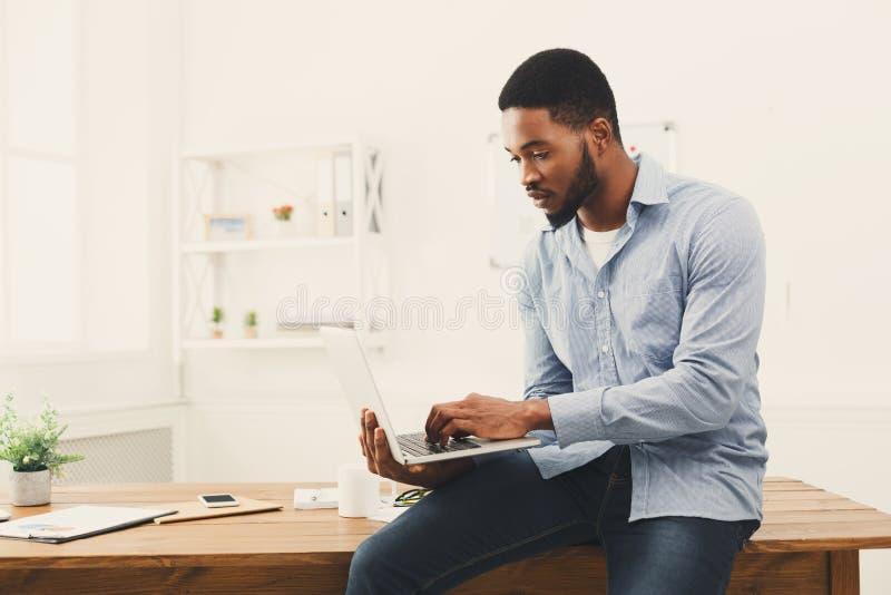 研究膝上型计算机的年轻黑商人在办公室 库存照片