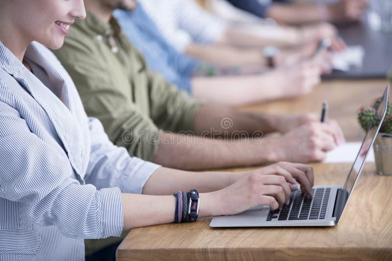 研究膝上型计算机的微笑的企业家 免版税库存图片