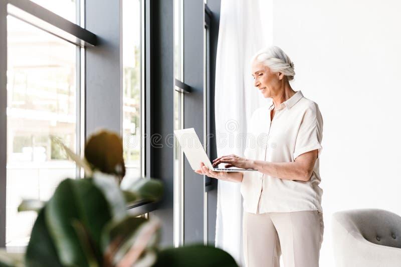 研究膝上型计算机的微笑的成熟的商业妇女 免版税库存图片