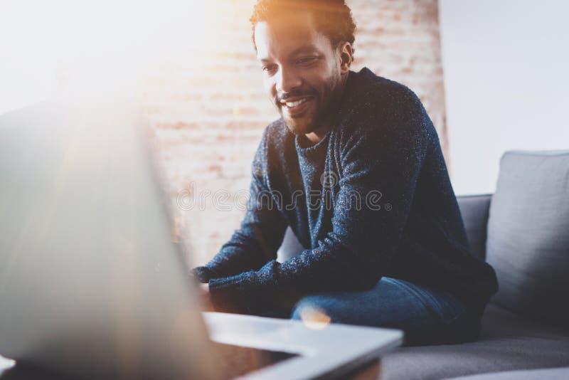 研究膝上型计算机的快乐的有胡子的非洲人,当坐沙发在他的现代办公室地方时 青年人的概念 免版税图库摄影