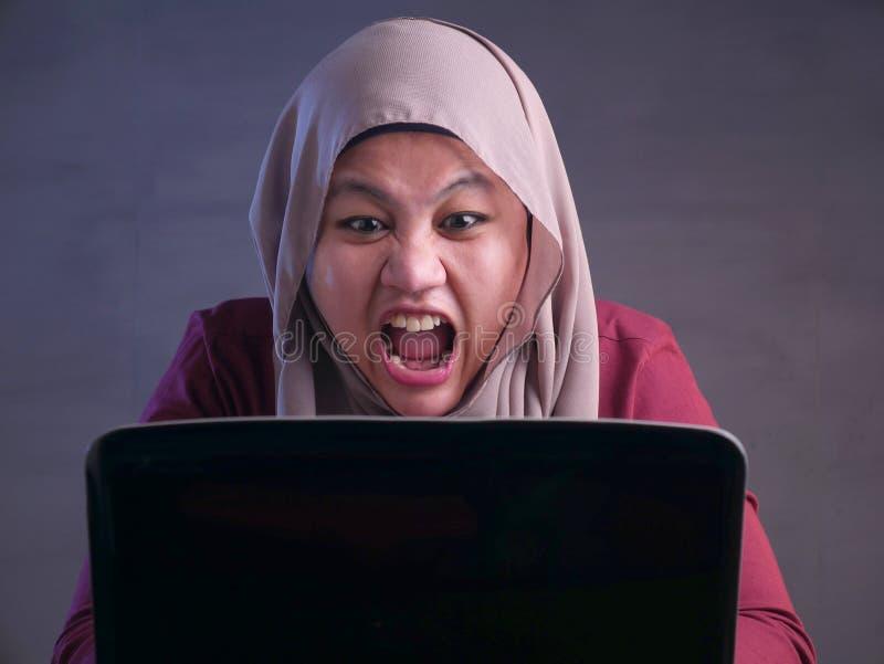 研究膝上型计算机的恼怒的回教女实业家在办公室 免版税库存照片