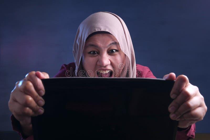 研究膝上型计算机的恼怒的回教女实业家在办公室 库存照片