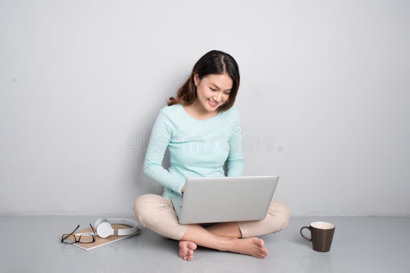 研究膝上型计算机的愉快的偶然美丽的亚裔妇女坐o 免版税库存照片
