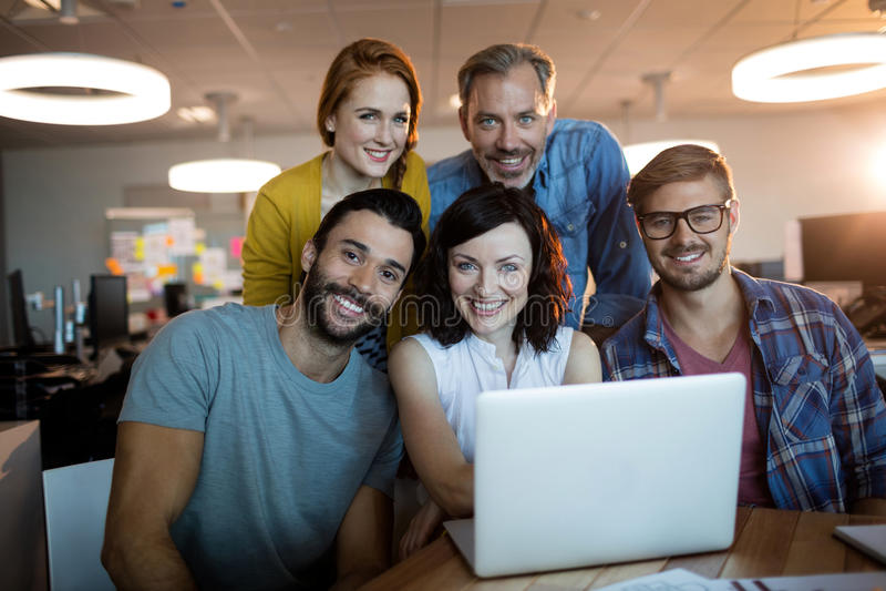 研究膝上型计算机的愉快的创造性的企业队画象  免版税库存照片