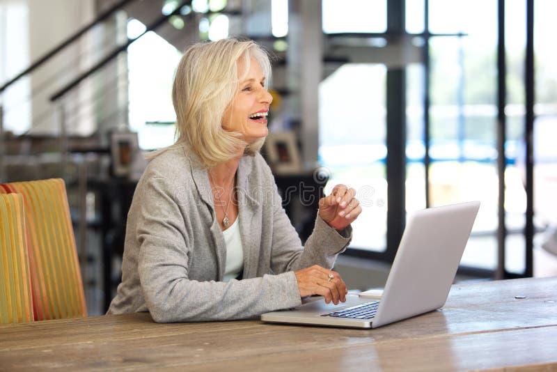 研究膝上型计算机的愉快的更老的女商人 免版税库存图片