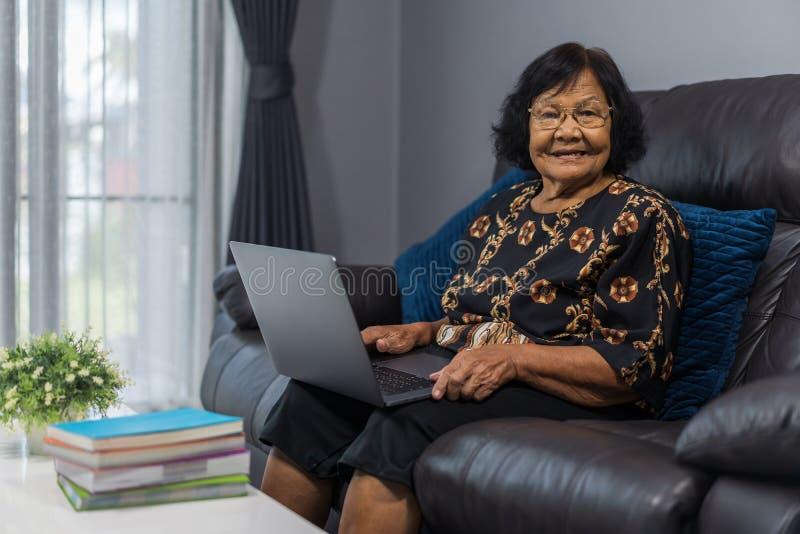 研究膝上型计算机的愉快的资深妇女在客厅 免版税库存图片