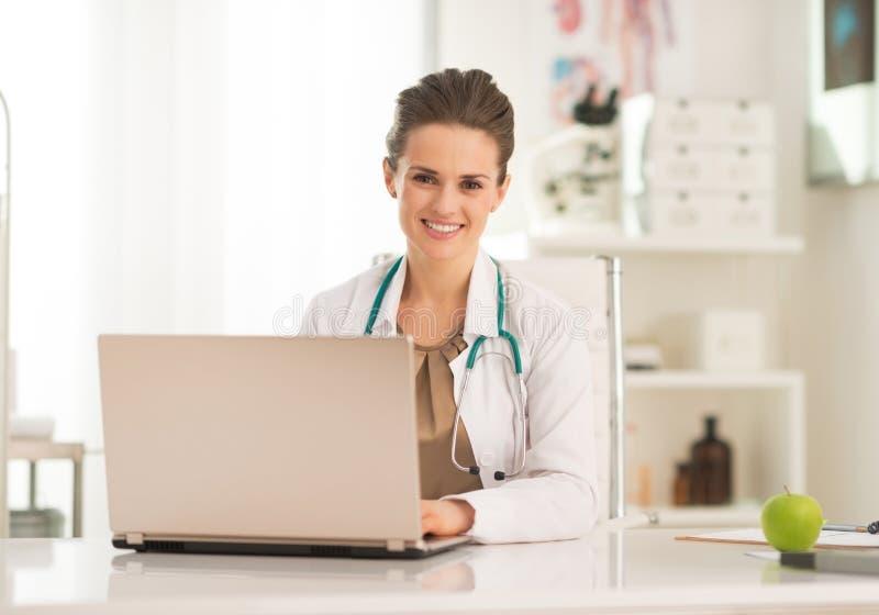 研究膝上型计算机的愉快的医生妇女 免版税库存图片