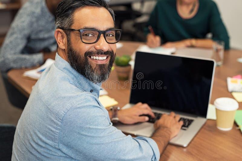 研究膝上型计算机的拉丁成熟商人 图库摄影