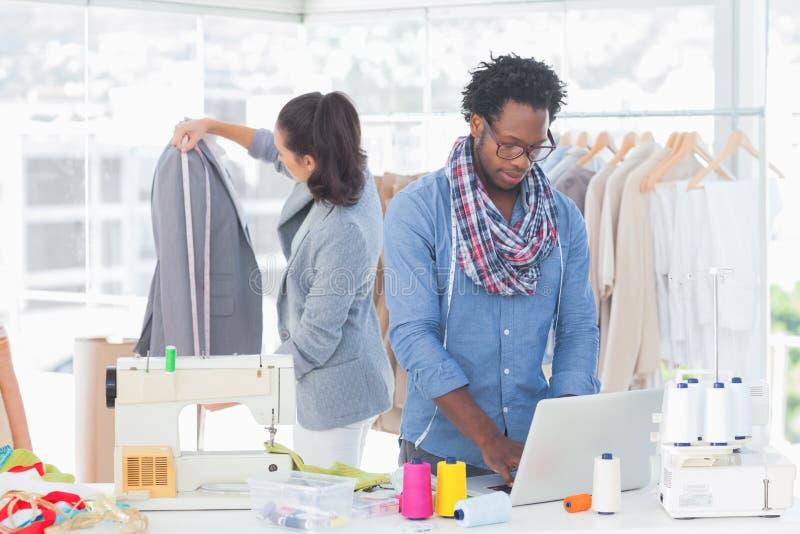 研究膝上型计算机的时装设计师 免版税库存图片
