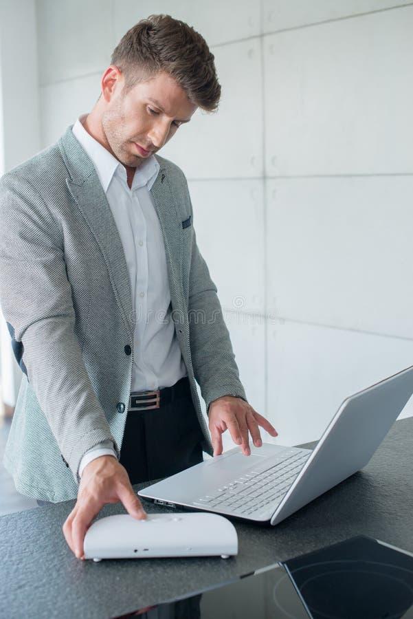 研究膝上型计算机的时髦的商人 免版税库存图片