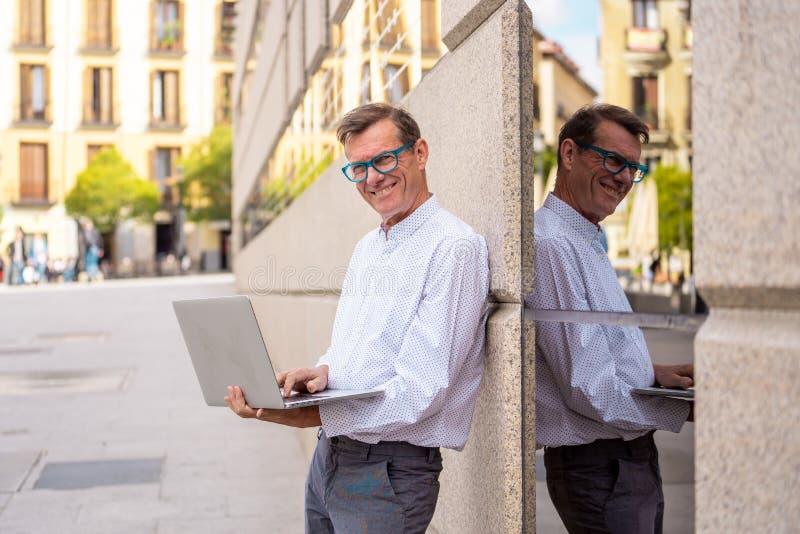 研究膝上型计算机的时髦的老人浏览互联网在数字游牧人的城市户外资深使用现代技术停留 免版税图库摄影