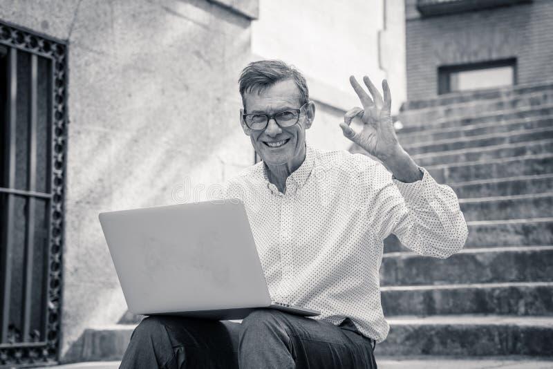 研究膝上型计算机的时髦的老人浏览互联网坐数字游牧人的台阶户外城市资深使用现代 免版税图库摄影