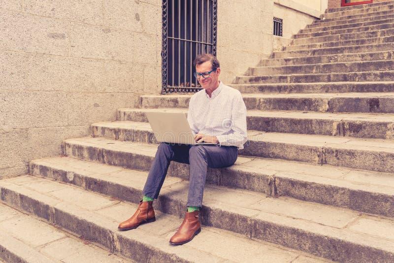 研究膝上型计算机的时髦的老人浏览互联网坐数字游牧人的台阶户外城市资深使用现代 免版税库存图片