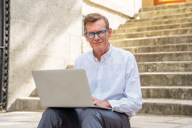 研究膝上型计算机的时髦的老人浏览互联网坐数字游牧人的台阶户外城市资深使用现代 免版税库存照片