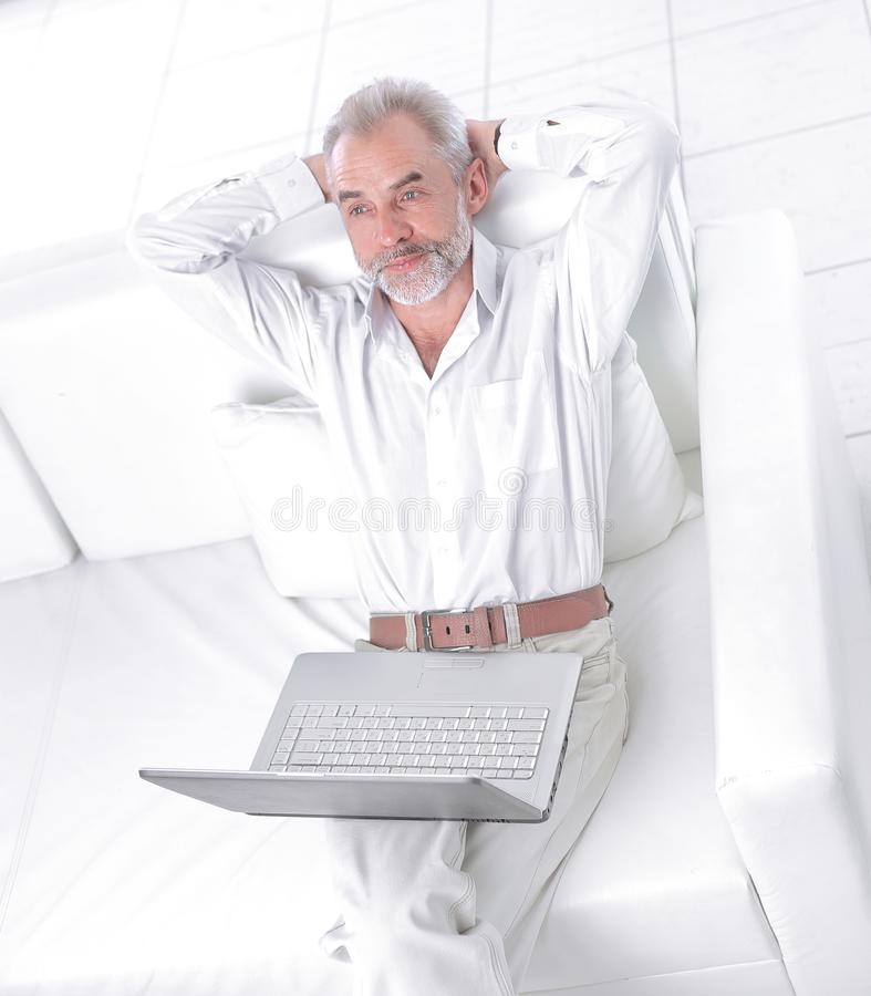研究膝上型计算机的沉思资深商人在办公室 免版税库存照片
