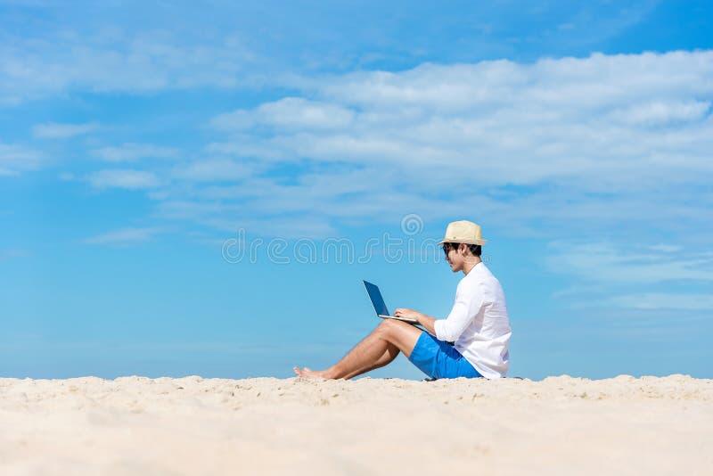 研究膝上型计算机的生活方式年轻亚裔人,当冷颤坐美丽的海滩,自由职业者的工作社会在假日夏天时 库存照片
