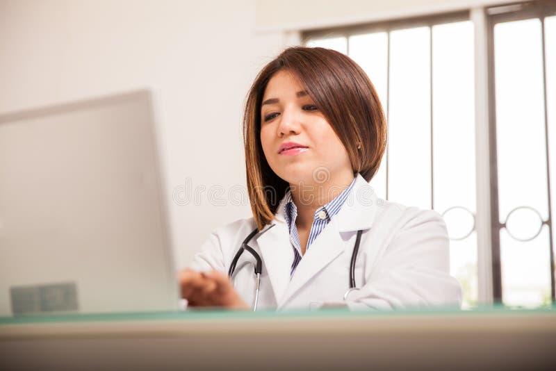 研究膝上型计算机的繁忙的医生 免版税图库摄影
