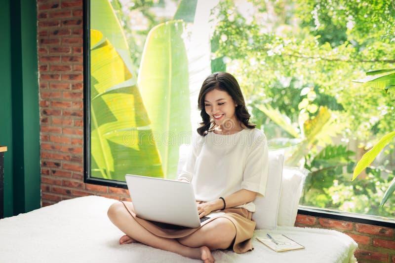 研究膝上型计算机的美丽的年轻微笑的妇女,当坐时 库存图片