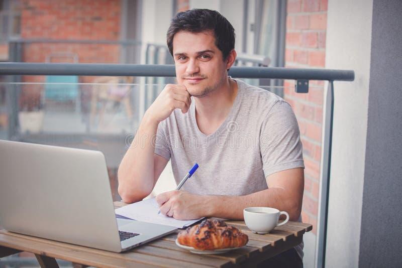 研究膝上型计算机的英俊的年轻经理 免版税库存照片