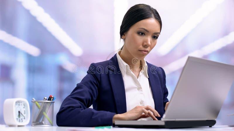 研究膝上型计算机的被启发的年轻新闻工作者在办公室,工作刺激,事业 库存图片
