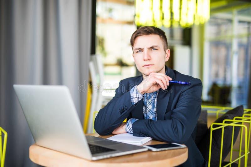 研究膝上型计算机的被拉紧的年轻人在咖啡馆桌和认为上 图库摄影