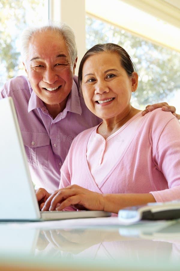 研究膝上型计算机的资深台湾夫妇 免版税库存图片