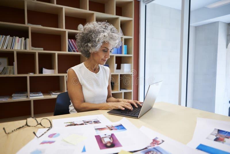 研究膝上型计算机的资深女实业家在办公室 库存照片