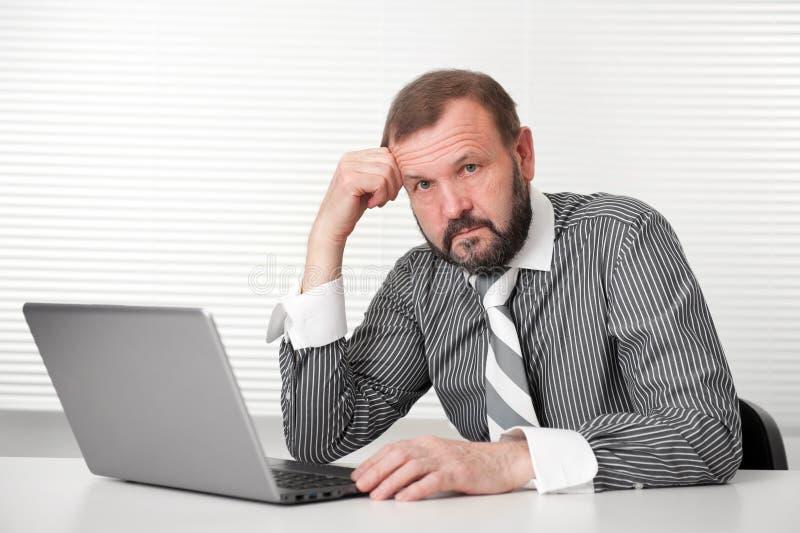 研究膝上型计算机的高级生意人 图库摄影