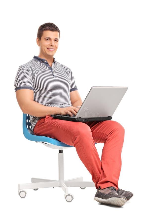 研究膝上型计算机的年轻人供以座位在椅子 库存图片